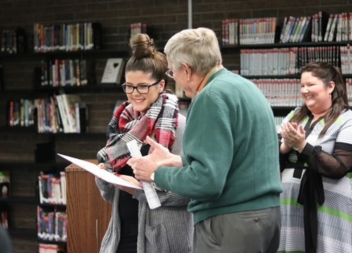 Lilly Smith receiving her award at the November board of education meeting by Forest Park Greenhills Kiwanis club member John Pennycuff. Photo by Drew Jackson.