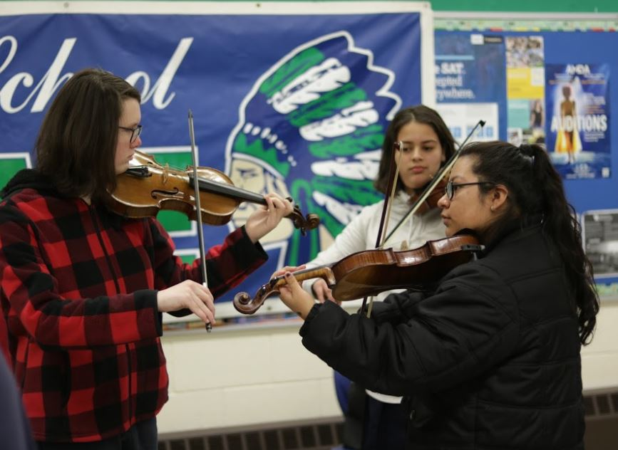 Winton Woods High School students play the restored violins together. Photo by Drew Jackson.
