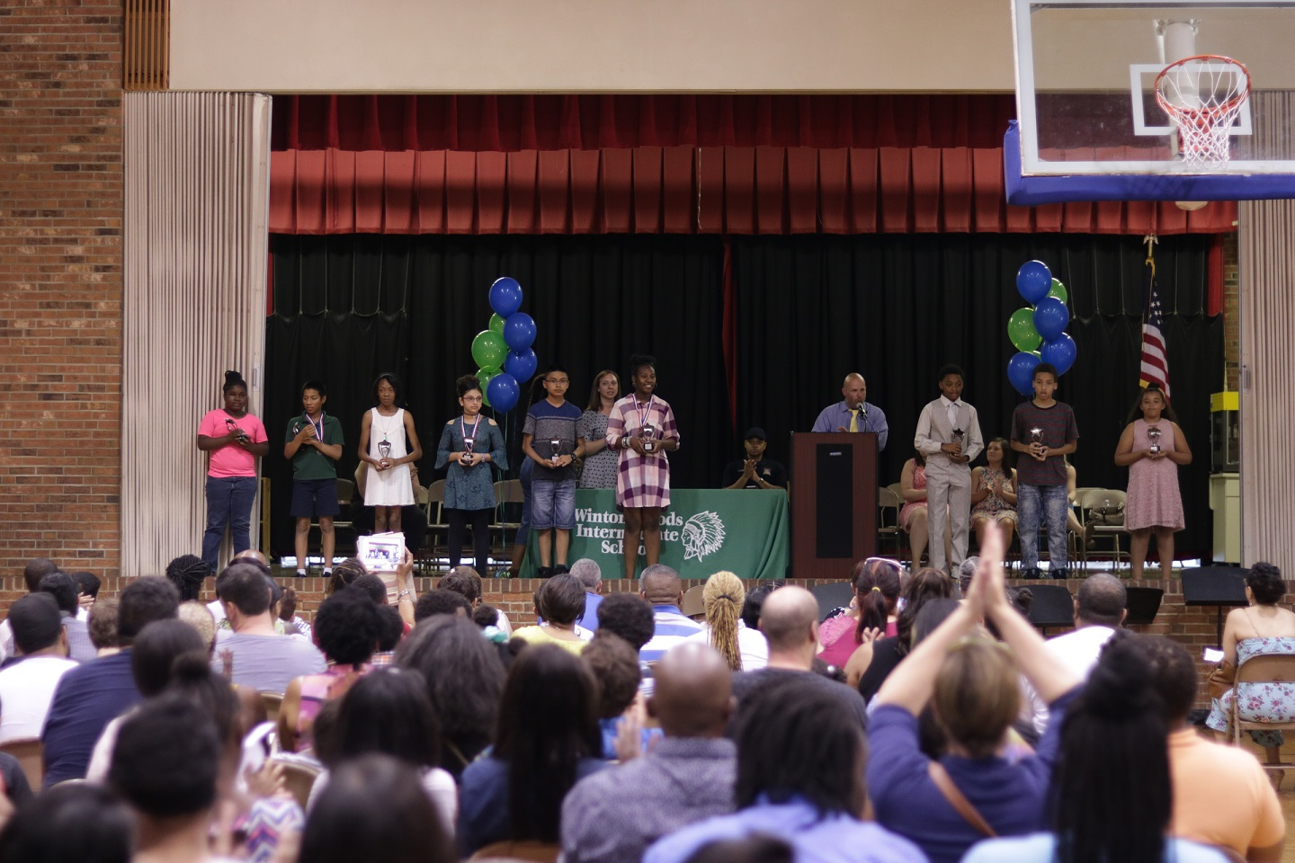 WWIS Principal Jeremy Day presents awards to students in the gymnasium. Photo by Drew Jackson.